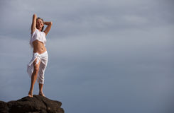 Pretty  woman stretching up tall on lava rocks Royalty Free Stock Images