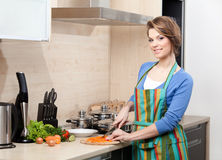 Pretty woman in striped apron cooks Stock Photo