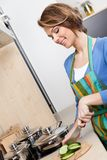 Pretty woman in striped apron cuts vegetables Royalty Free Stock Photography