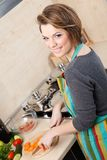 Pretty woman in striped apron slices vegetables Stock Photo
