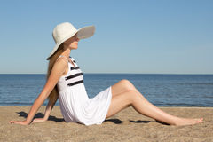 Pretty woman in striped dress and hat sitting on the beach Royalty Free Stock Photos