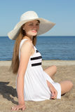 Pretty woman in striped dress sitting on the beach Stock Images