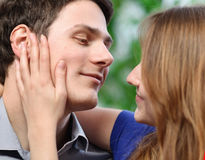 Pretty woman stroking the cheek of her boyfriend with love Stock Image