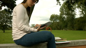 Pretty woman studying with books and tablet stock video