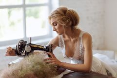 Pretty Woman. In the style of Coco Chanel sitting on a sewing machine royalty free stock images