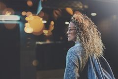 Pretty woman in stylish clothing wearing eye glasses traveling in the european night city. Bokeh and flares effect on. Blurred background royalty free stock image