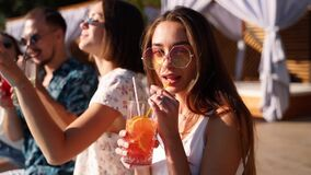 Pretty woman in stylish sunglasses toasting with friends, drinking cocktail of plastic straw at pool party. Group of