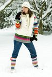 Pretty Woman sucking on a candy cane in the snow. A beautiful woman in colorful striped boots with a matching sweater sucking on a candy cane in a provocative Royalty Free Stock Photos