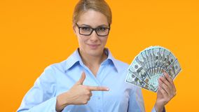 Pretty woman in suit pointing finger into bunch of dollars, profitable business stock video
