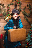 Pretty woman with  suitcase in christmas interior Royalty Free Stock Images