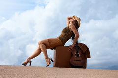 Pretty woman with suitcase and guitar Stock Images