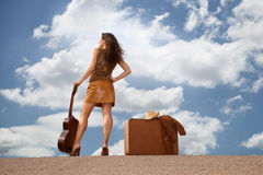 Pretty woman with suitcase and guitar Royalty Free Stock Image