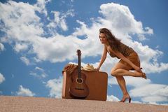 Pretty woman with suitcase and guitar Stock Photography