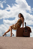 Pretty woman with suitcase and guitar Royalty Free Stock Photos