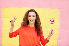 Pretty woman in summer clothes showing peace and holding lolipop. Fashion portrait pretty woman in summer clothes showing peace and holding lolipop over colorful Stock Photography