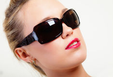 Pretty woman in sunglasses. Portrait of brightly lit beautiful young woman in sunglasses Stock Photo