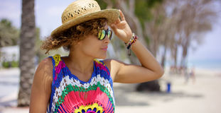 Pretty woman in sunglasses adjusting hat Stock Images