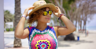 Pretty woman in sunglasses adjusting hat Royalty Free Stock Photo