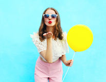 Pretty woman in sunglasses with air balloon sends an air kiss over colorful blue. Background Royalty Free Stock Photos