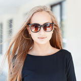 Pretty woman in sunglasses on background of windows.On a sunny d. Ay stock photography