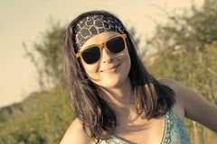 A pretty woman in sunglasses looking into a camera royalty free stock image