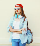 Pretty woman in sunglasses and red cap with headphones over white Royalty Free Stock Image