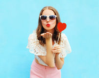 Pretty woman in sunglasses with red heart lollipop sends an air kiss over colorful blue. Background Royalty Free Stock Photography