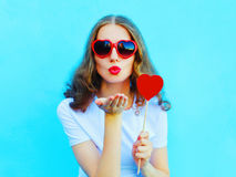 Pretty woman in sunglasses with red heart lollipop sends an air kiss over colorful blue Stock Photos