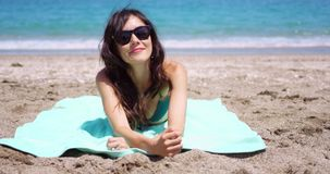 Pretty woman in sunglasses sunbathing on a beach stock video