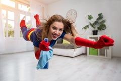Pretty woman superhero flying through the room with a mop. Attractive woman superhero flying through the room with a mop stock photography