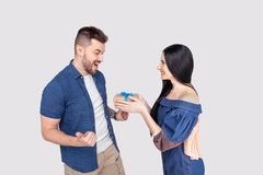 Pretty woman surprising her boyfriend with gift isolated wearing denim clothing on ashy-gray background royalty free stock photo