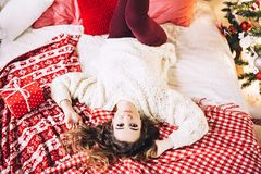 Pretty woman in sweater lies on the sofa with present gift for christmase, shiny christmas tree, garlands and balls, new Stock Photography