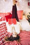 Pretty woman in sweater lies on the sofa with present gift for christmase, shiny christmas tree, garlands and balls, new Royalty Free Stock Photography