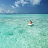 Pretty woman swimming in canoe and relax in the sea. Happy island lifestyle. White sand, crystal-blue sea of tropical beach. stock images