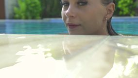 Pretty woman in swimming pool at summer vacation in resort. Portrait cute girl swimming in outdoor pool at sunny day stock video