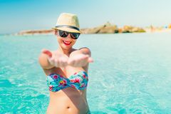 Pretty woman in swimsuit and straw hat smiling on tropical beach, enjoying sunny days and vacation. Woman in swimsuit and straw hat smiling on tropical beach stock photos