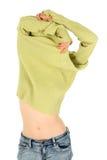 Pretty woman takes off a green sweater. Pretty woman in jeans takes off a green sweater Stock Image