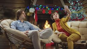 Pretty woman takes photo of herself with her man on Christmas night. Attractive adult woman takes photo of herself with young man on Christmas night sitting by stock video footage