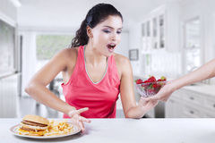 Pretty woman takes strawberry and refuse burger Royalty Free Stock Photos