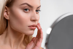 Pretty woman taking care of her face Stock Images
