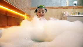 Pretty woman taking foamy bath and playing with soap foam Royalty Free Stock Photography