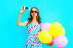 Pretty woman taking a picture on a smartphone with an air colorful balloons Royalty Free Stock Photo