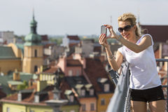 Pretty  woman taking pictures on his smartphone old european city from the observation deck. Royalty Free Stock Images