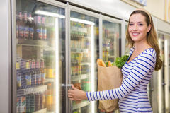 Pretty woman taking product on fridge Royalty Free Stock Photography