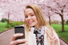 Pretty woman taking self portrait at spring blossom park. Pretty young female model gesturing peace sign while taking her picture with cell phone. Beautiful Stock Photography