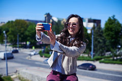 Pretty woman taking selfie in front of city panorama stock photo
