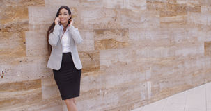 Pretty woman talking on phone and leaning on wall Stock Photography