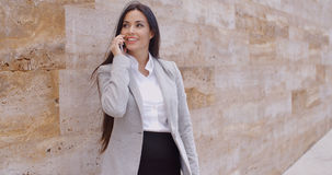 Pretty woman talking on phone and leaning on wall Royalty Free Stock Photography