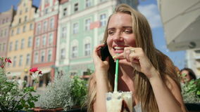 Pretty woman talking on a smartphone and drinking coffee in a cafe Royalty Free Stock Photos