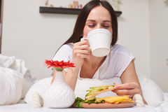 Pretty woman tasting cup of aromatic and eating fresh sandwich stock image